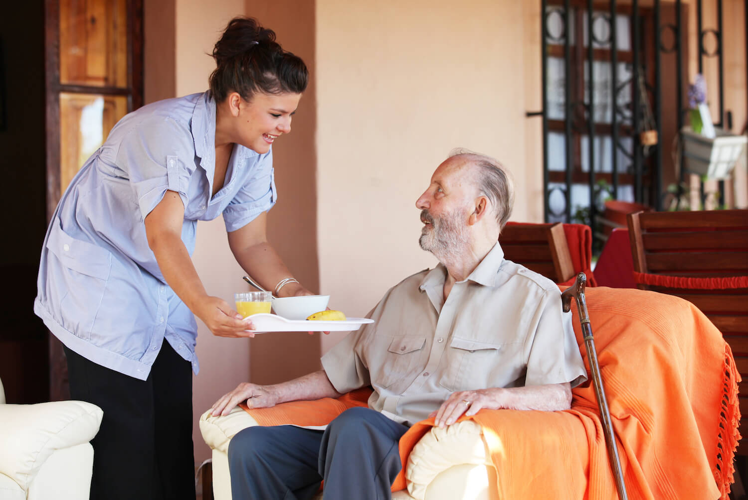 Home Healthcare worker assisting a senior at their home with meal preparation.